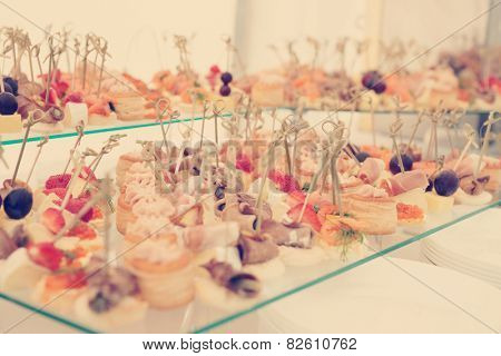 Fish, meat and cheese snacks in plate on banquet table, toned image