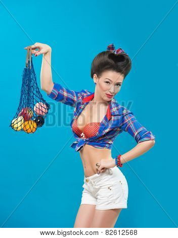 woman with pin-up make-up with a bag of fruit