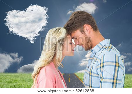 Attractive couple standing touching heads against cloud heart