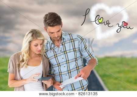 Attractive couple working out their finances against road on grass