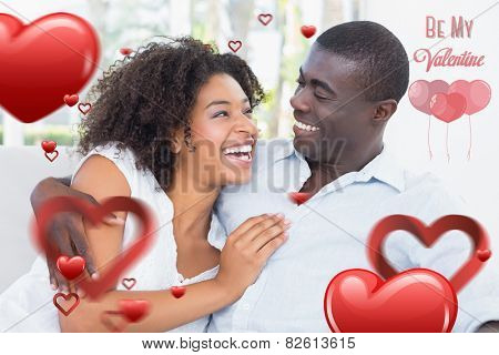 Attractive couple cuddling on the couch against cute valentines message