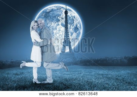 Happy couple posing in trench coats against large moon over paris