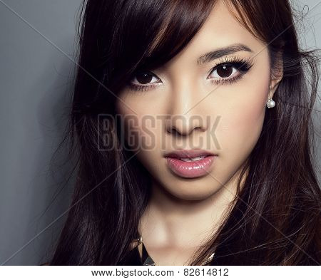young beautiful asian woman with perfect skin and pretty make-up and brown hair