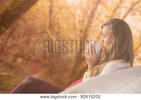 Pretty blonde relaxing on the couch with tea against tranquil autumn scene in forest