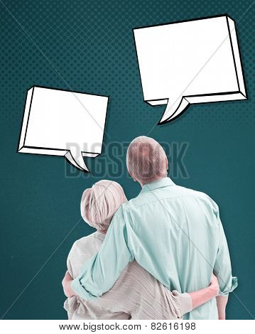 Mature couple hugging and looking against teal