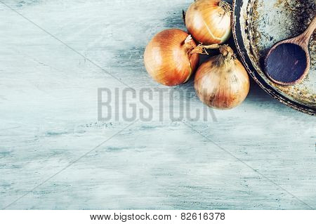 Old kitchen pan wooden spoon three onions wooden table.