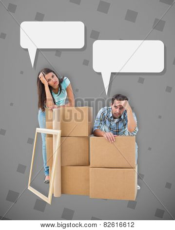 Stressed young couple with moving boxes against grey