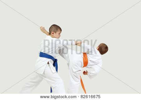 On a gray background two sportsmen are doing paired exercises karate