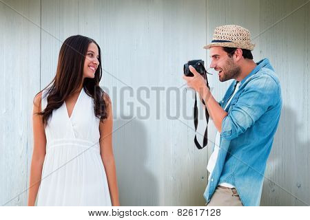 Handsome hipster taking a photo of pretty girlfriend against wooden planks