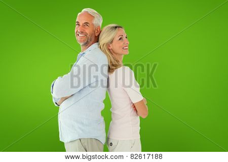 Smiling couple standing leaning backs together against green vignette