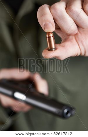 Soldier Shows Cartridge From Gun