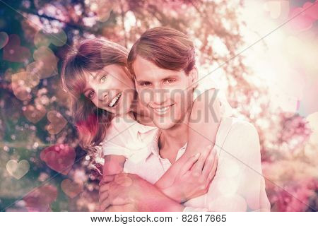 Man giving his pretty girlfriend a piggy back in the park smiling at camera on a sunny day