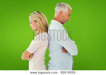 Unhappy couple not speaking to each other against green vignette
