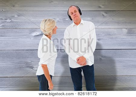 Annoyed woman being ignored by her partner against bleached wooden planks background