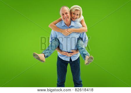 Mature man carrying his partner on his back against green vignette