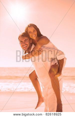 Smiling man giving happy girlfriend a piggy back at the beach