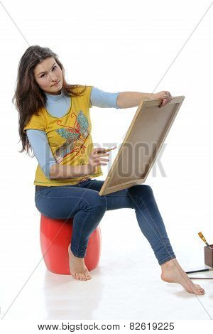 The Artist Paints A Picture Of An Easel Holding On Her Lap
