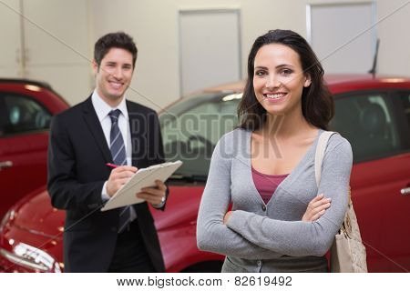 Smiling businessman undersign a car contract at new car showroom