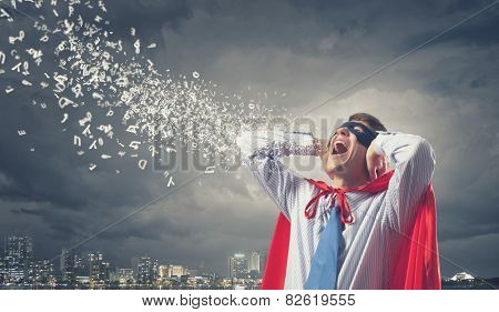 Young man in hero costume closing ears with palms
