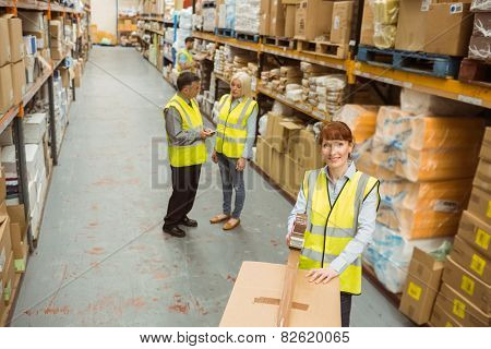 Warehouse worker sealing cardboard boxes for shipping in a large warehouse