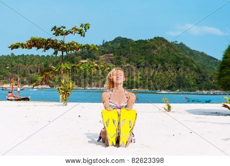Young woman doing yoga with flippers on the beach