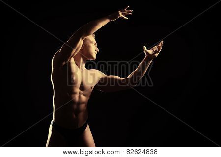 Handsome muscular athletic man posing over black background. Men's beauty. Bodybuilding. Sports.