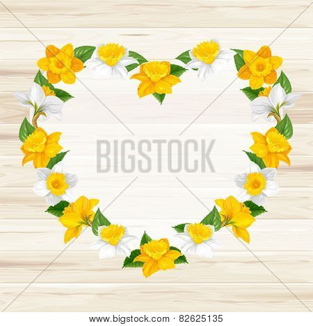 Romantic frame from daffodils flowers (in heart shape) on wooden background