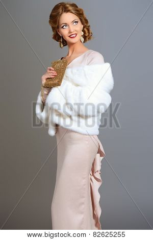 Beauty, fashion and luxury concept. Elegant young woman with evening make-up and hairstyle posing in beautiful dress and white mink fur jacket. Jewellery. Studio shot.