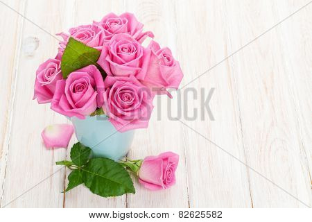 Fresh spring garden pink roses bouquet on white wooden table with copy space