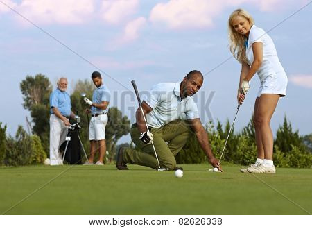 Pretty female golfer learning to putt on the green from male instructor.