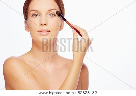 Charming girl applying eyeshadows with brush