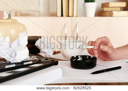 Female hand with cigarette at desktop with moving clapper and working mess on light cupboard background