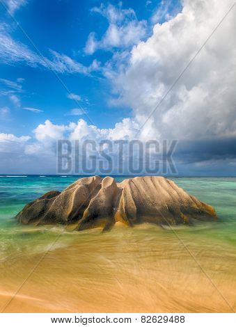 Beautifully shaped granite boulder is washed by sea at Anse Source d'Argent beach, La Digue island, Seychelles. Long daytime exposure