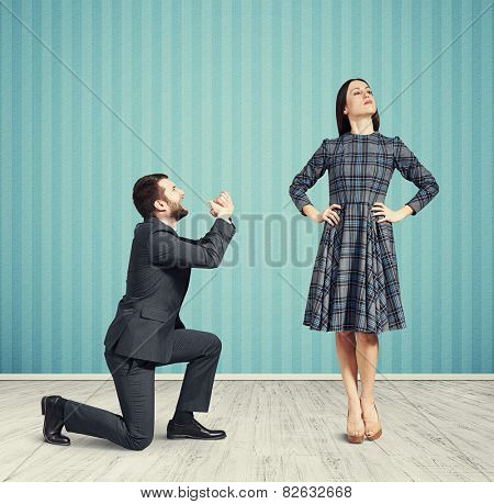 crying man looking at alluring woman and asking for forgiveness. photo in empty room with blue wall