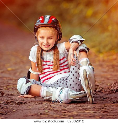happy little girl sitting on roller skates in the autumn forest