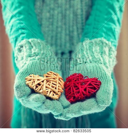 Woman hands in light teal knitted mittens are holding a beautiful red hearts. Love and St. Valentine concept. Instagram filter.