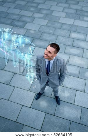 business, development and people concept - young smiling businessman with world map hologram outdoors from top
