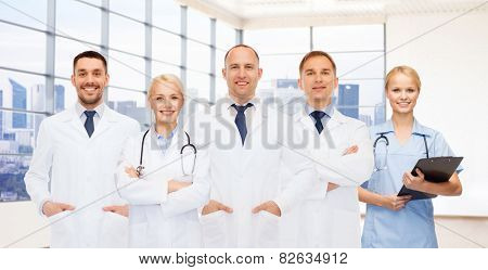 medicine, profession, teamwork and healthcare concept - group of smiling medics or doctors with clipboard and stethoscopes over clinic background