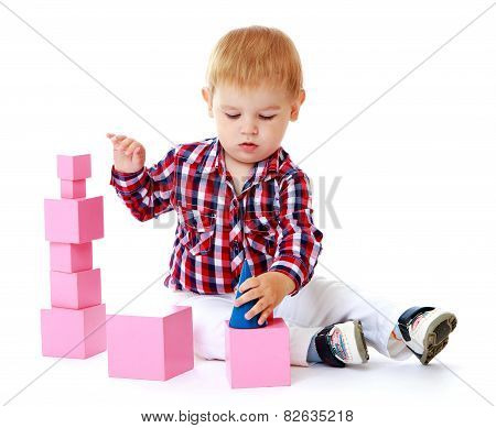 Caucasian beautiful little boy sitting on the floor and adds cub