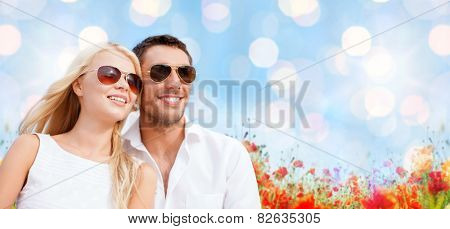 summer holidays, people and dating concept - happy couple in shades over blue lights and poppy field background