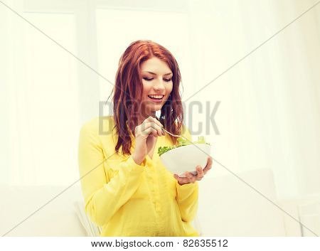 health, dieting, home and happiness concept - smiling young woman eating green salad at home