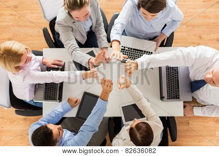 business, people, technology and team work concept - close up of creative team with laptop and tablet pc computers showing high five gesture and sitting at table in office