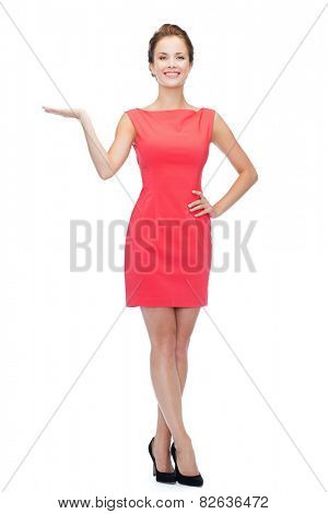advertising and people concept - smiling young woman in red dress holding something on palm of her hand