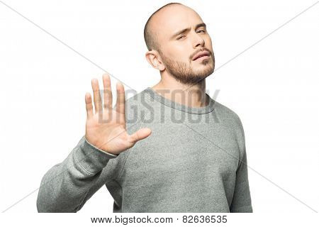 Portrait of handsome young man requiring stop with his hand, isolated on white