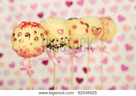 Tasty cake pops on color background