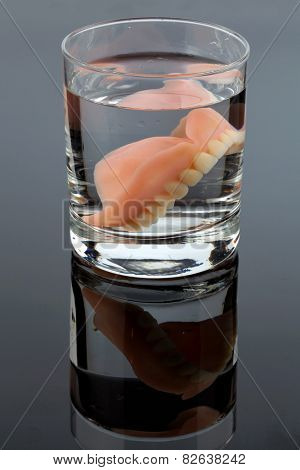 denture m water glass, symbolic photo for dentures and care