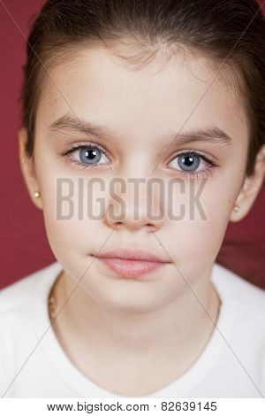 studio portrait of a pretty little girl on a burgundy background