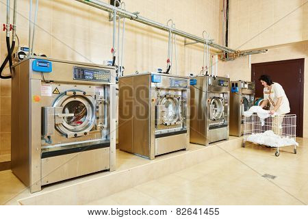 cleaning services. Woman loading laundry washing machine with cloth