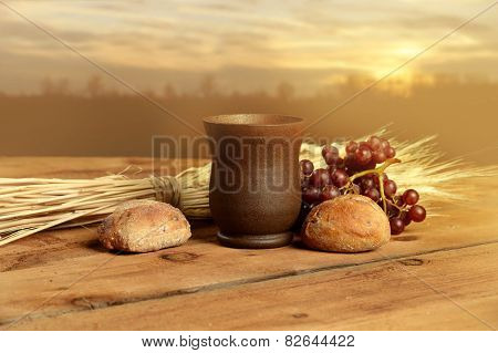 Cup of wine, bread. grapes and wheat on vintage table with warm sunset in background