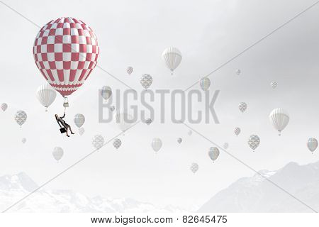 Businesswoman flying on aerostat balloon high in sky